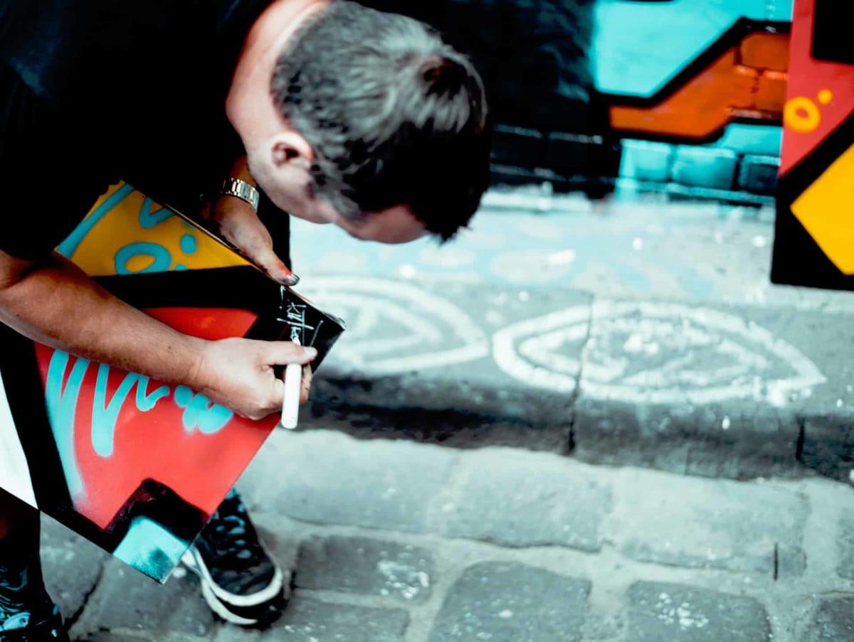 An artist signs a piece of work on the street.