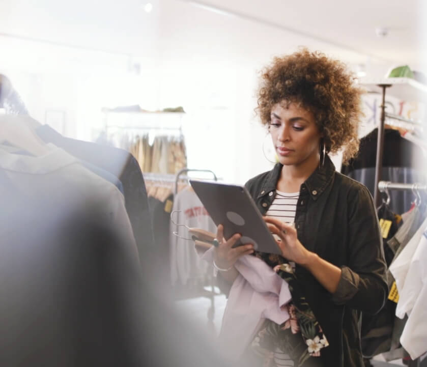 A lady is stood in a clothes store using a tablet