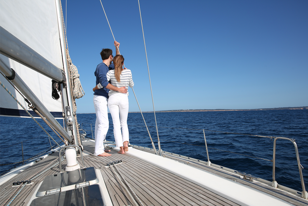Yacht charter: couple sailing blue sky.