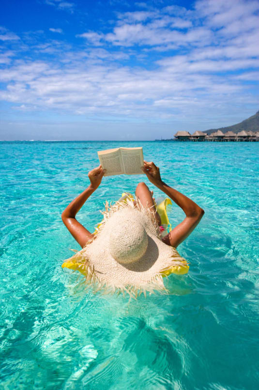 woman reading on raft in turquoise waters