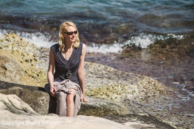 Woman sunbathing on a rock