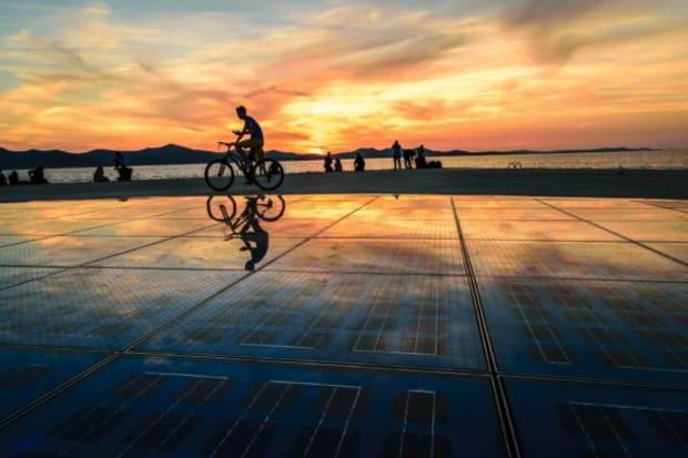 boy biking the greeting to the sun zadar croatia sunset