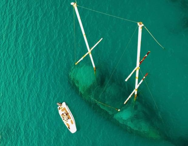 boat near ship wreck in sea