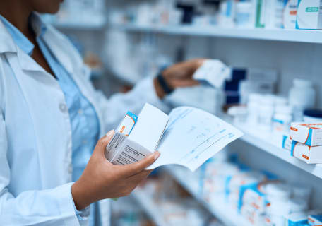 female pharmacist with packets of drugs in her hand